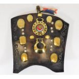 Lot 104 - An antique leather shield with various horse brass