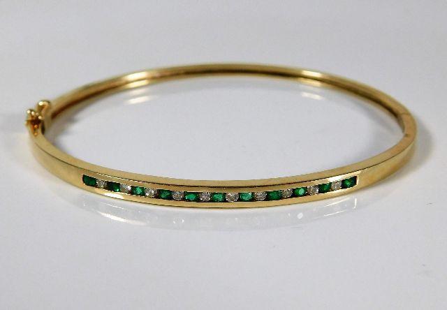 Lot 347 - A 10ct gold bangle set with emerald & 0.2ct diamon