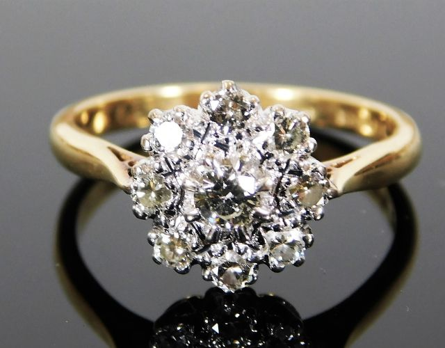 Lot 302 - An 18ct gold daisy style ring set with approx. 0.6