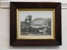 An oak framed photograph of the building of the Ro