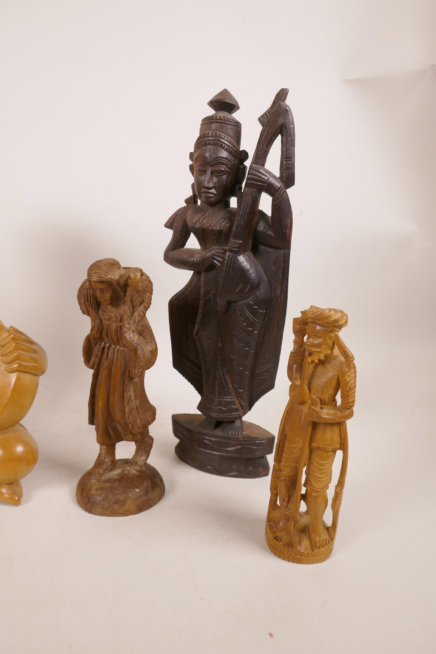 Lot 41 - Three Balinese carved wood figures of musicians, together with three other carved wood figures,