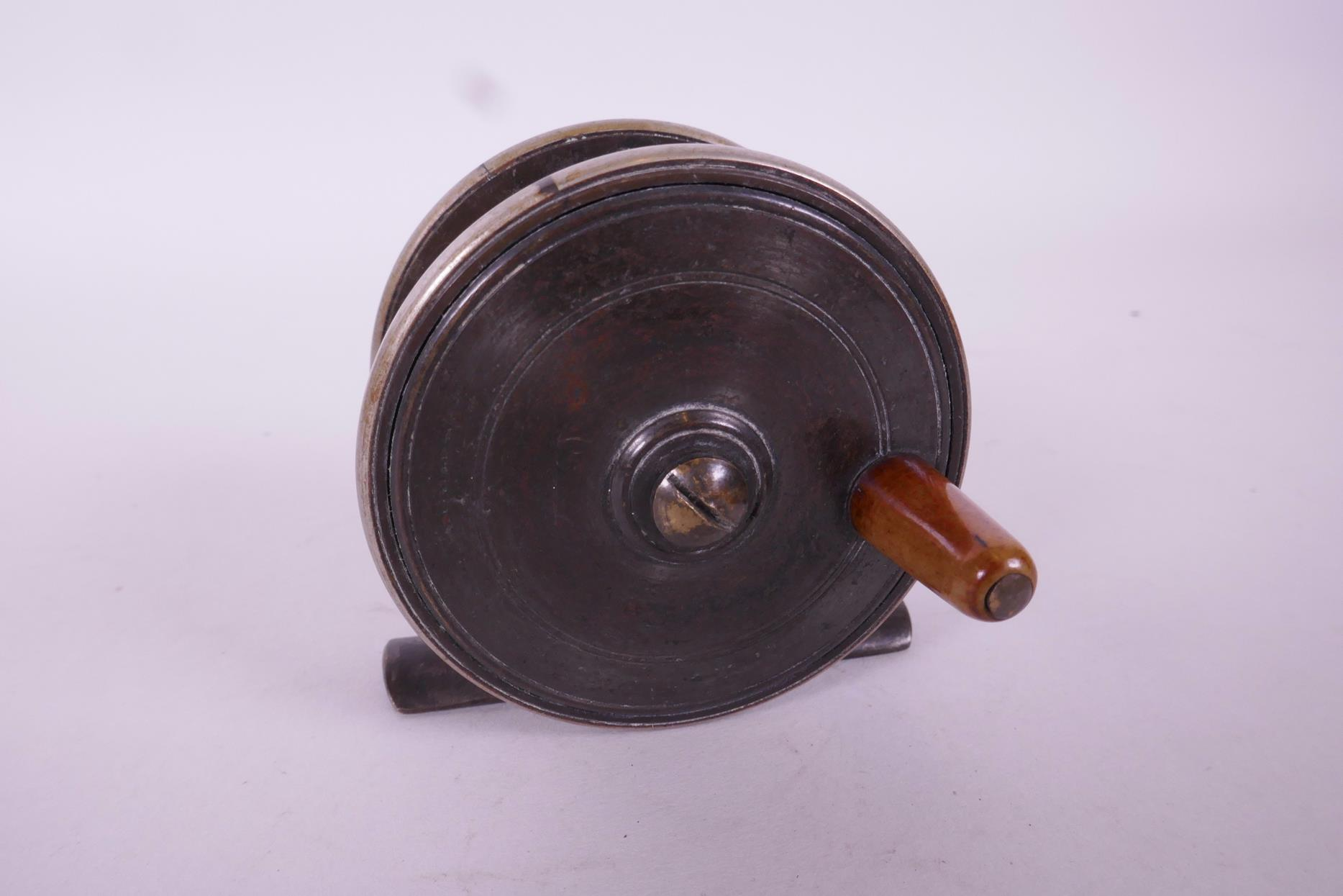 """Lot 79 - A 2½"""" brass and Bakelite trout fishing reel"""