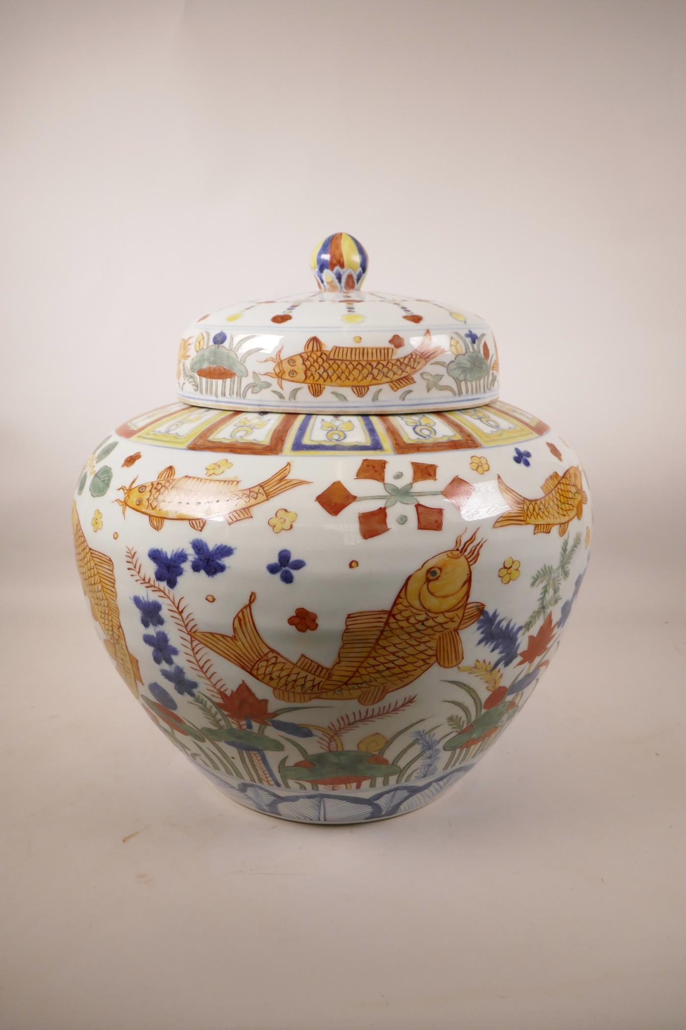 Lot 56 - A large Ming style wucai pottery jar and cover decorated with carp in a lotus pond, 6 character mark