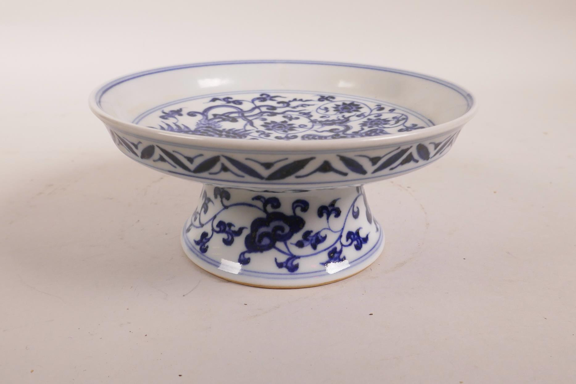 Lot 80 - A Chinese blue and white stem dish with scrolling lotus flower and phoenix decoration, 6 character