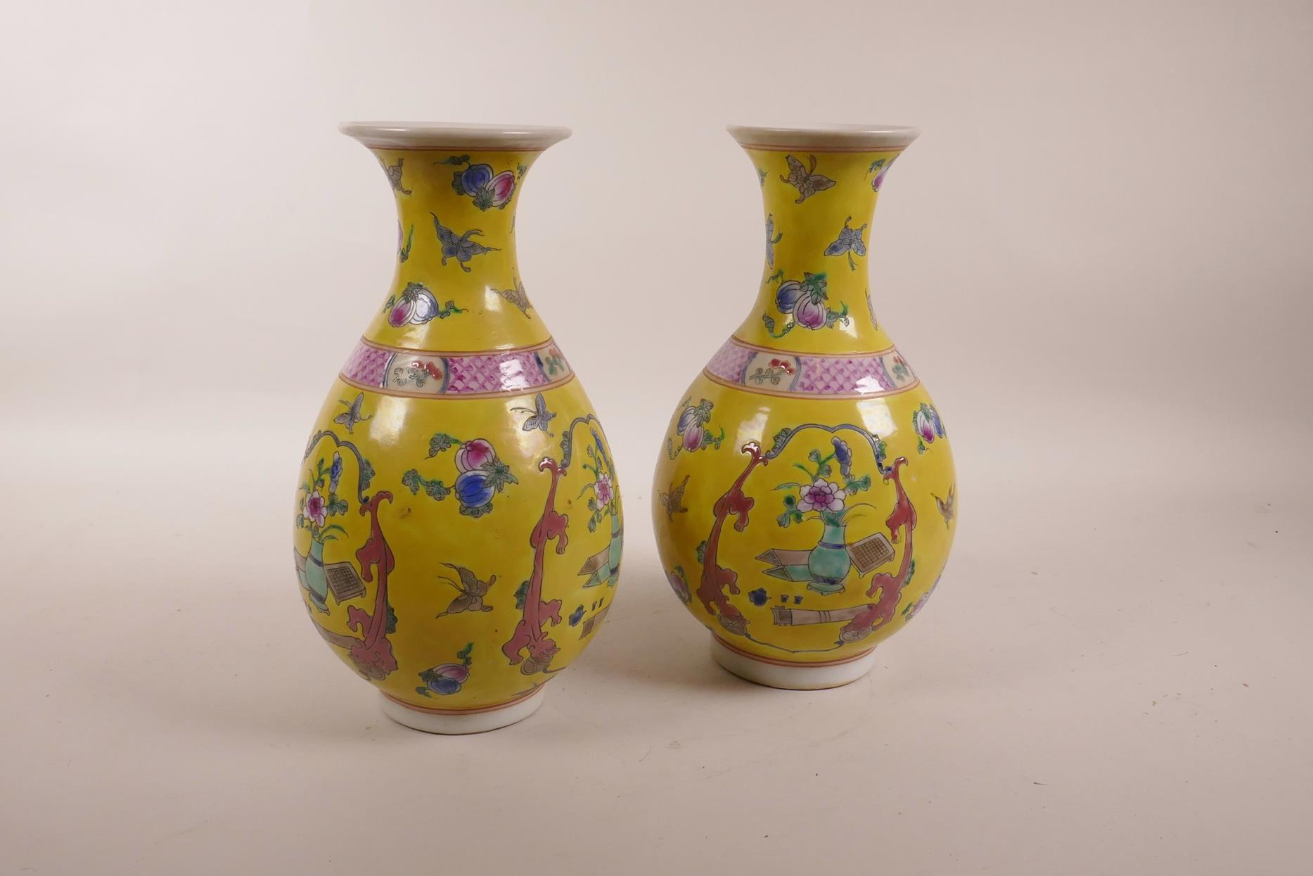 Lot 83 - A pair of Chinese yellow ground porcelain pear shaped vases decorated in polychrome enamels