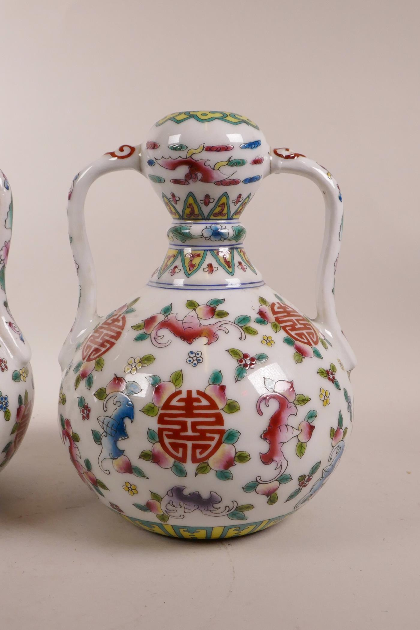 Lot 70 - A pair of Chinese polychrome porcelain garlic head shaped vases with two handles, decorated with