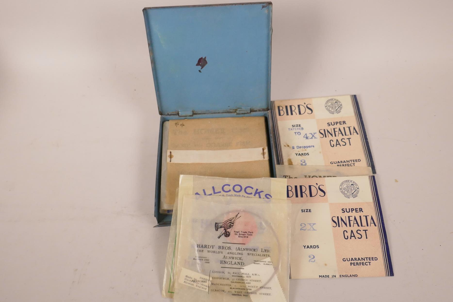 Lot 42 - A vintage metal fishing line box, with a selection of fine casting lines from Hardy, Birds, Allcocks