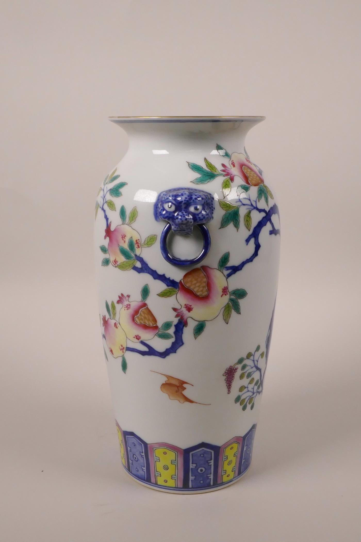 Lot 43 - A Chinese polychrome porcelain vase with twin mask handles and fruiting pomegranate tree decoration,
