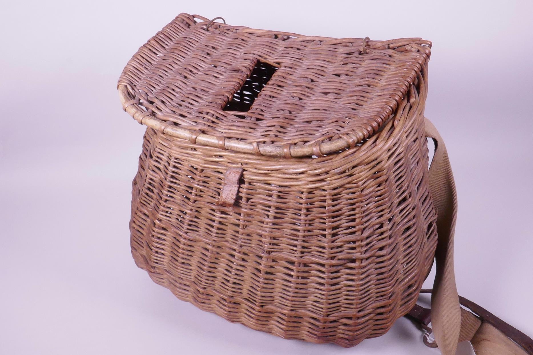 """Lot 30 - A vintage woven wicker fishing basket, 11"""" wide"""
