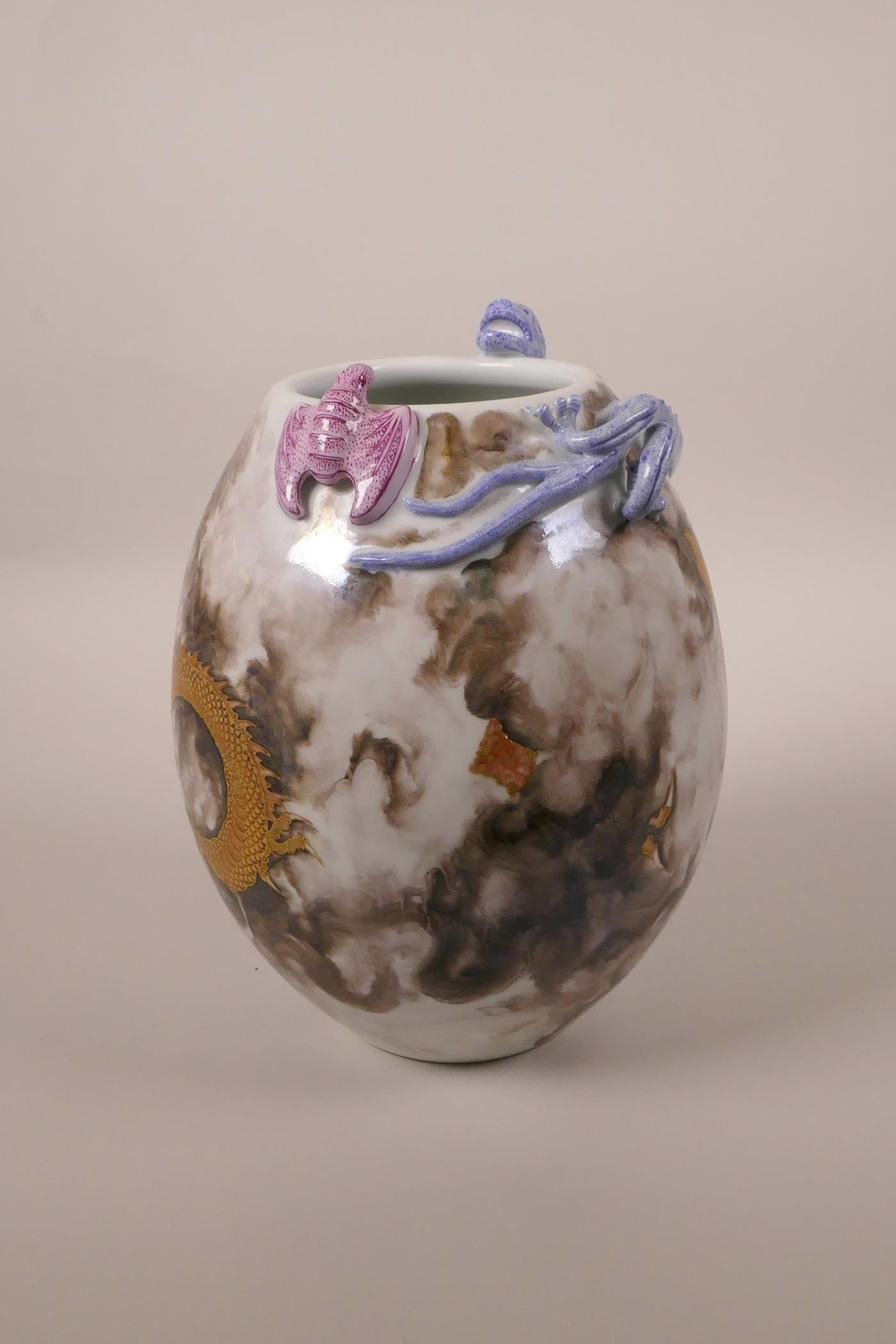 Lot 23 - A Chinese polychrome porcelain vase with applied dragon and bat decoration to the lip and red and