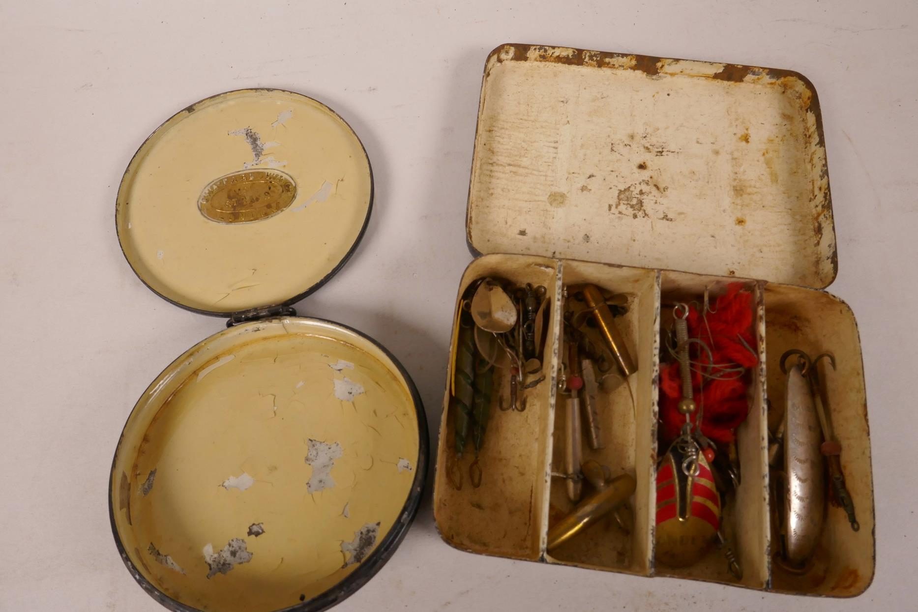 """Lot 6 - A small vintage lure box, 4¼"""" x 3"""" x 1"""", containing various lures, together with a round Chas Farlow"""