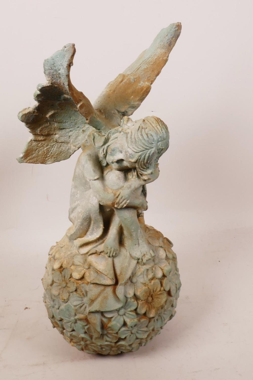 "Lot 6 - A cast iron garden figurine of a fairy seated on a flower, 12½"" high"