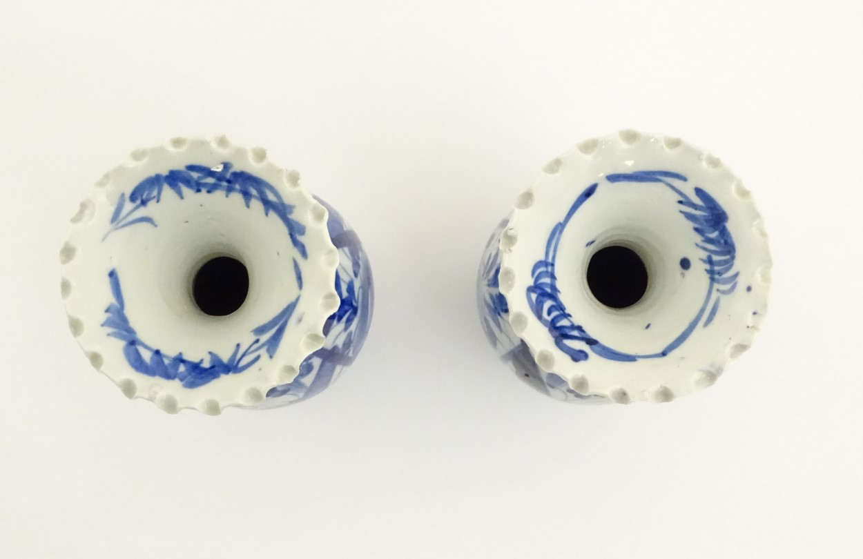 Lot 23 - A pair of blue and white Japanese vases with ribbon rims decorated with flowers. Approx.