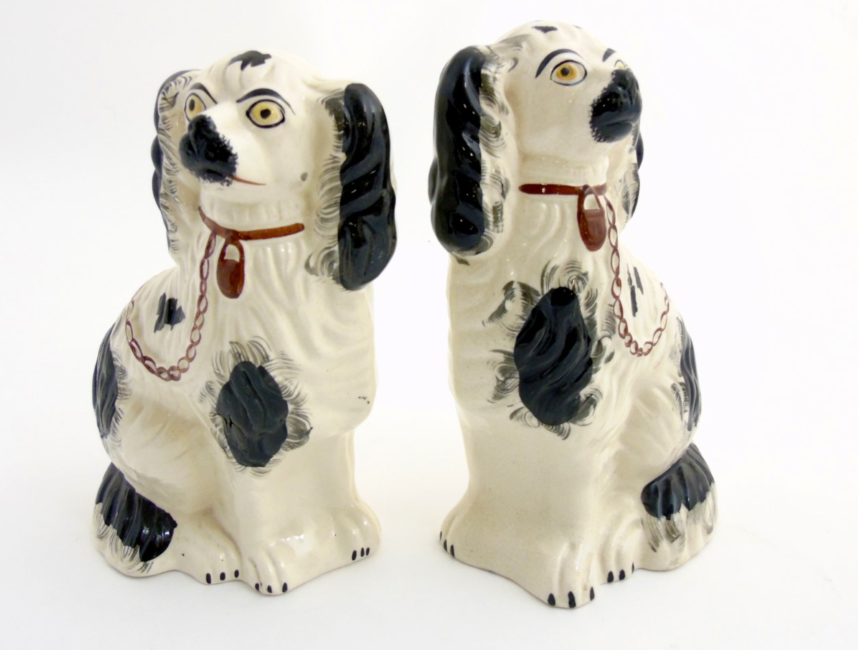 Lot 50 - Two Victorian Staffordshire spaniels, with black patch decoration and brown lock and chain,