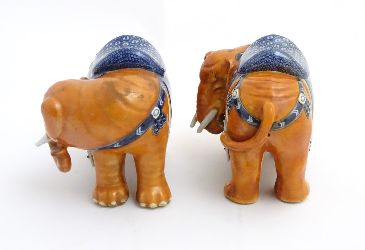 Lot 1 - A pair of Chinese ceramic elephants with rust coloured bodies and blue and white patterned saddles.