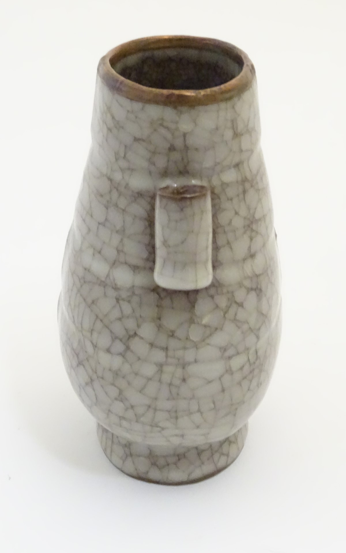 Lot 16 - A Chinese Ge vase with a crackle glaze, twin tubular handles and a copper rim. Approx.