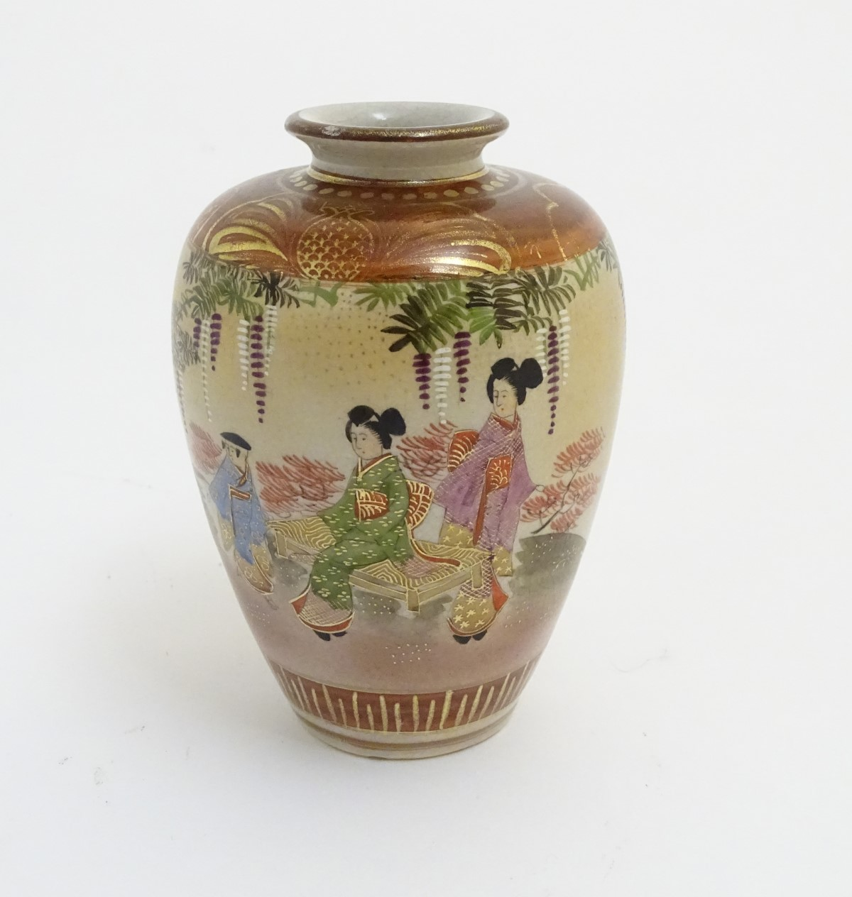 Lot 27 - A small Japanese satsuma vase depicting figures in a garden, with gilt highlights.