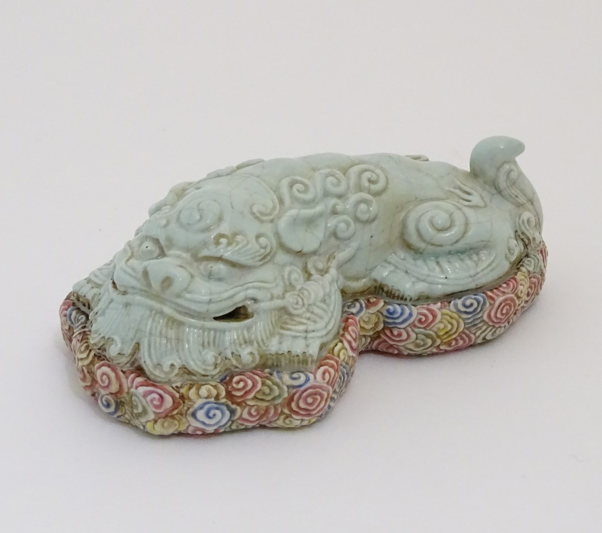 Lot 28 - A recumbent Chinese foo dog with a crackle glaze lying on a bed of stylised clouds.