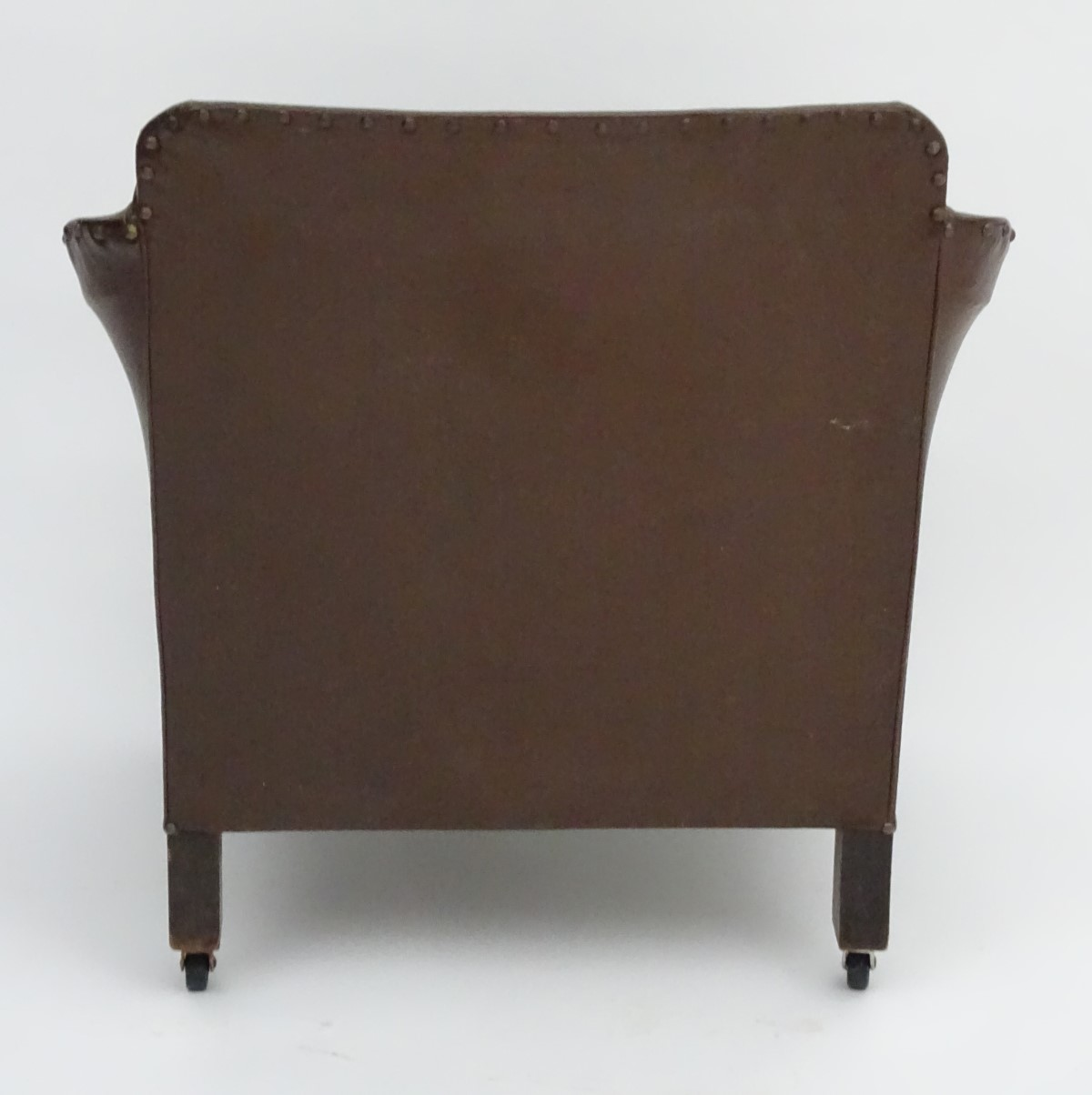 Lot 27 - An early / mid 20thC armchair with brass stud detailing,