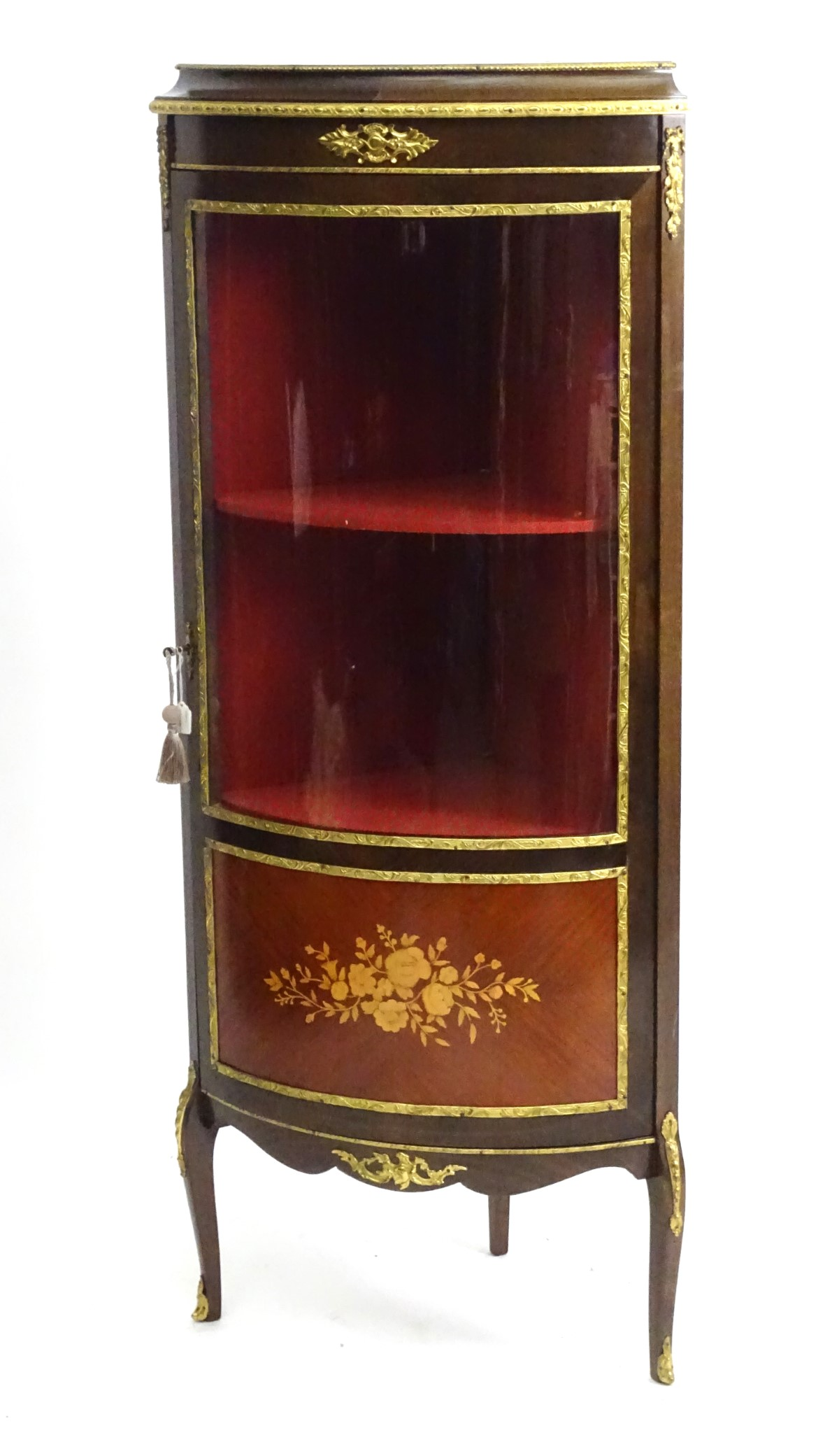 Lot 55 - A late 20thC free standing corner cabinet, having gilt mounts and banding throughout,