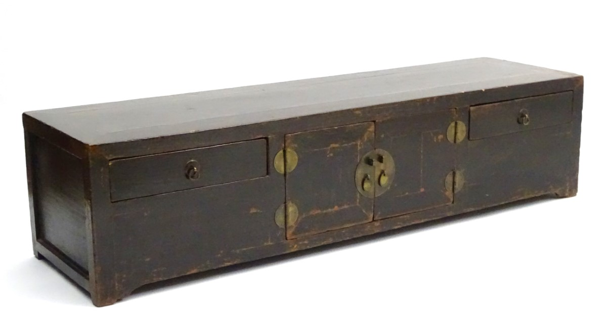Lot 14 - A 19thC Oriental low cupboard, of elm construction with four drawers, brown painted finish,
