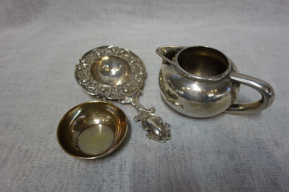 Lot 396 - A RUSSIAN METALWARE CREAM JUG, a Russian silver dish with stylised border and a white metal