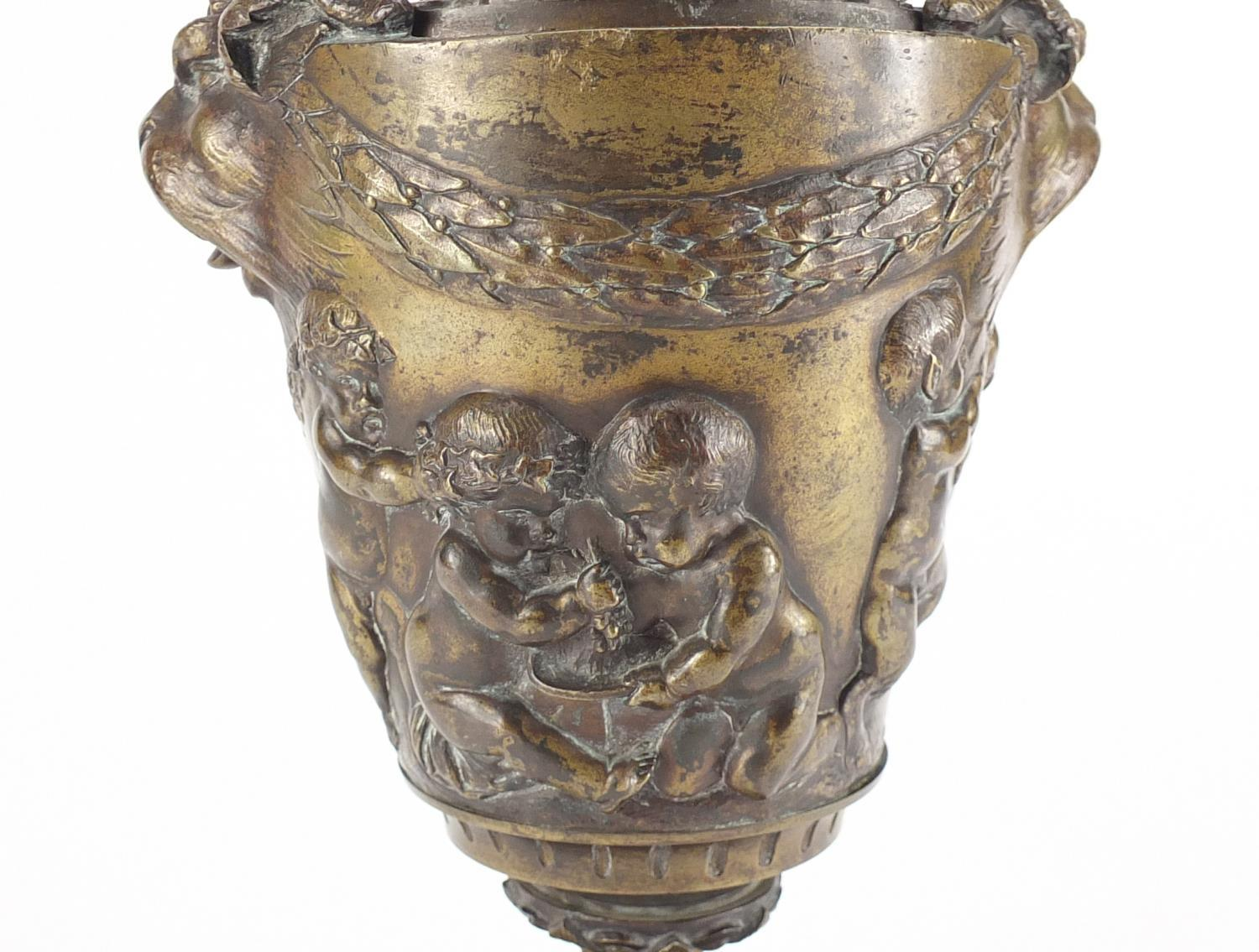 Lot 13 - 19th century classical patinated bronze urn and cover with rams head handles, cast in relief with