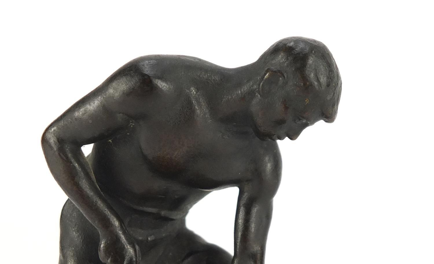 Lot 9 - Johann Robert Korn, patinated bronze of a young man with a pick axe, raised on a naturalistic