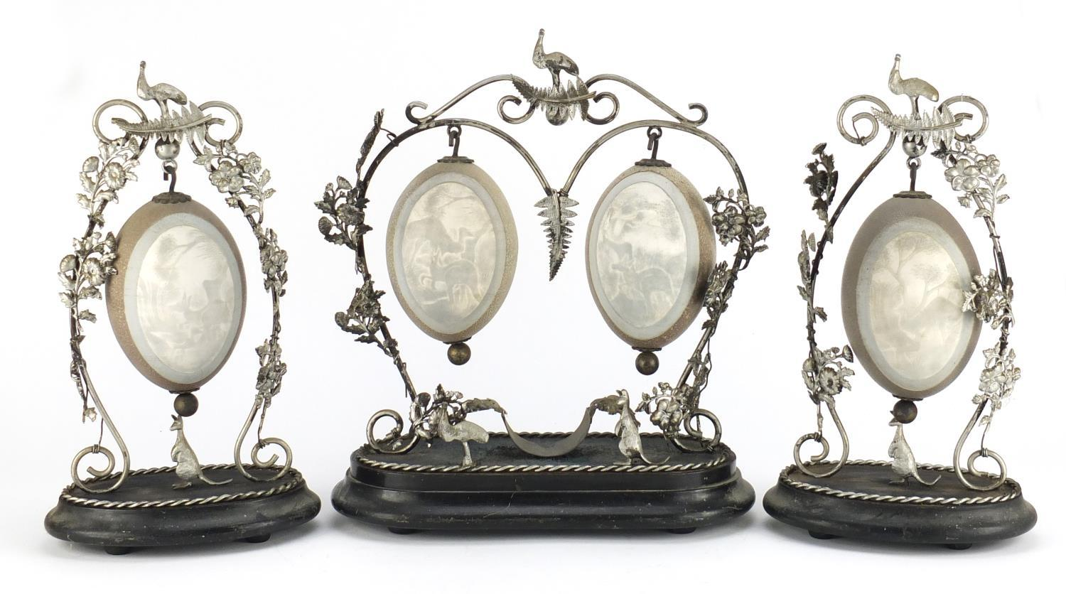 Lot 23 - Australian emu egg garniture with silver coloured metal mounts, the eggs carved with kangaroo's