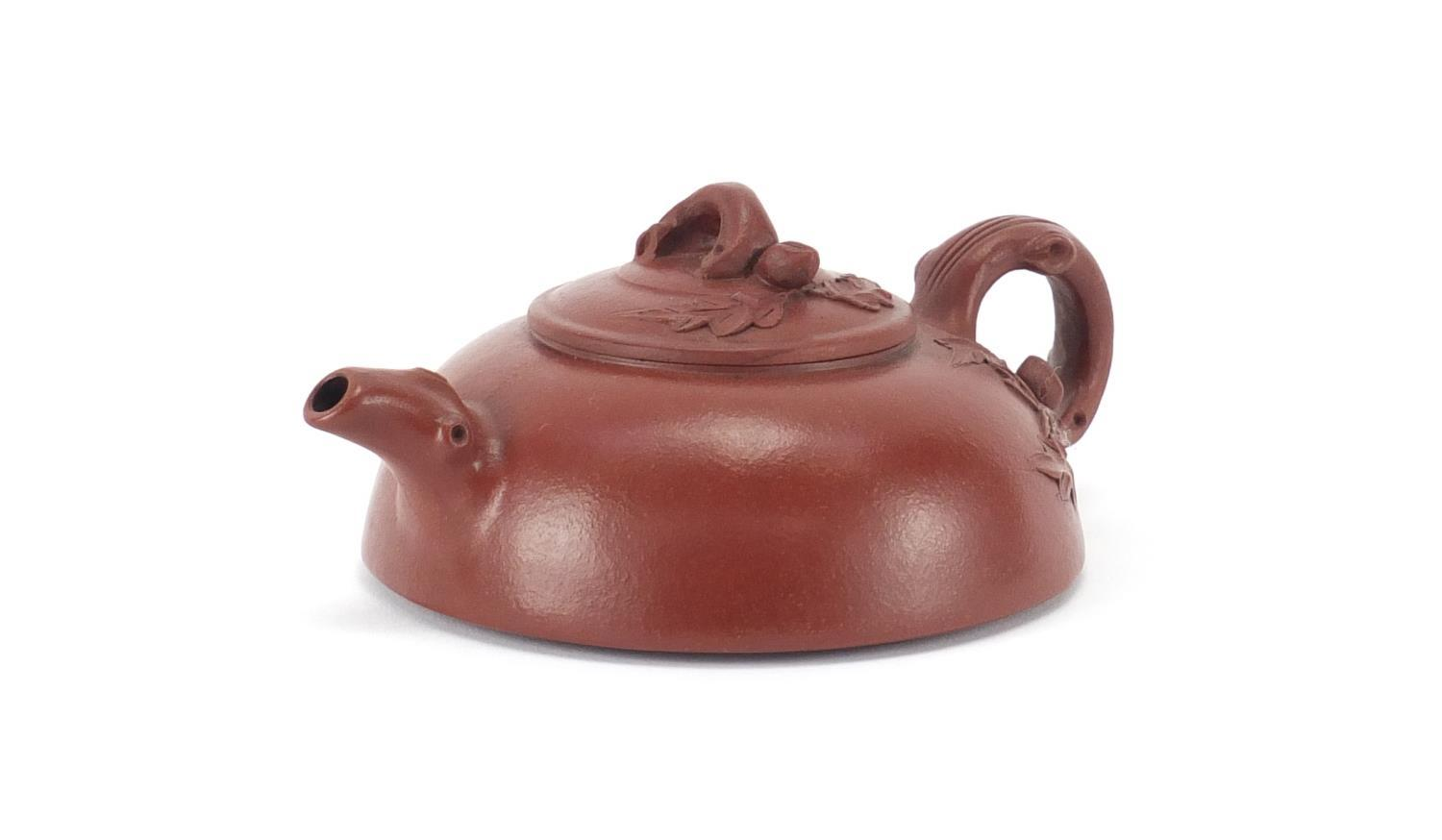 Lot 202 - Chinese yixing terracotta squatted teapot with naturalistic handle and spout, impressed marks to the
