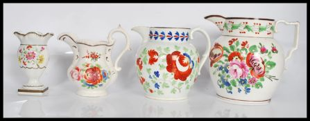A group of three 19th Century Staffordshire jugs all having hand painted floral sprays to include