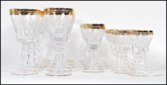A large collection of glassware having scrolled decoration to the bowls raised on knopped columns on
