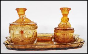 An early 20th Century Art Deco 1930's amber glass dressing table vanity set consisting of