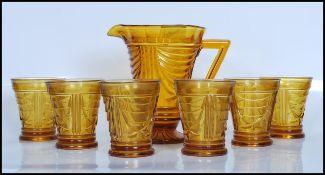 An early 20th Century Art Deco pressed amber glass lemonade set, comprising lemonade jug and a set