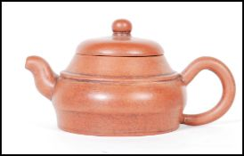 An early 20th Century Chinese Yixing teapot modelled in a brown clay with shaped handle and spout.