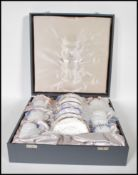 A cased Wedgwood bone China coffee can service for six in the Cavendish pattern. Gilt and cobalt