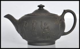 A 19th Century Victorian Wedgwood Jasperwareblack basalt teapot and cover havingrelief decorated