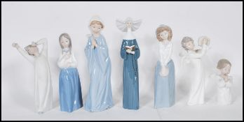A collection of Nao and Lladro ceramic figurines to include a Lladro nun, a Lladro praying cherub,
