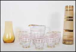 A mid 20th Century lemonade set consisting of a lemonade pitcher together with matching glasses
