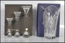 A boxed set of threeXavier Crystal candlesticks of graduating form having shaped rounded tops and