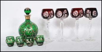 A believed 19th century Loetz manner silver overlay green glass Bohemian decanter and shot glass set