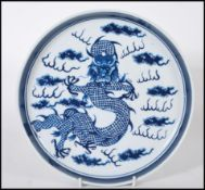 A 19th Century Chinese ceramic plate being hand painted in blue depicting a five toed dragon to