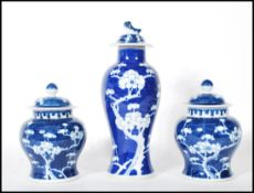 A harlequin garniture of three Chinese blue and white lidded jars to include a pair of ginger jars