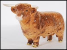 A Beswick ceramic figurine of a Highland cattle bull being stamped for Beswick, England to the foot.