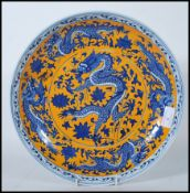 A 20th Century Chinese wall charger having hand painted on a yellow ground with five toed blue and