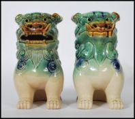 A pair of mid 20th Century Chinese porcelain temple lions / dogs of Fu. Both modeled with a jade