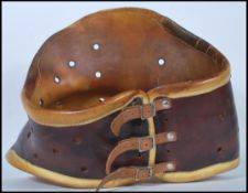 A 20th Century two tone leather medical back brace