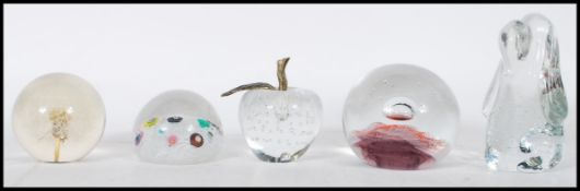 A collection of glass paperweights to include a li