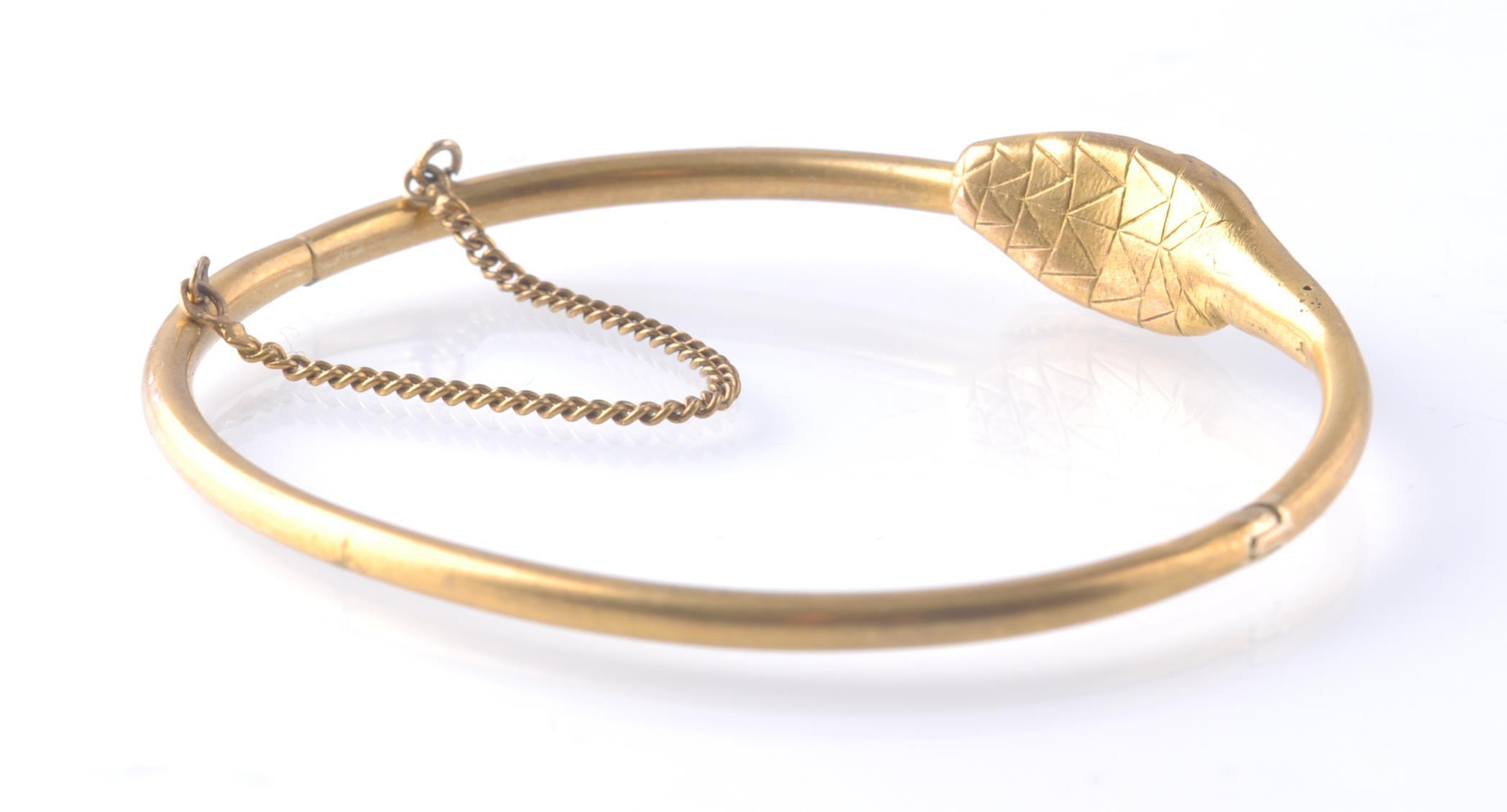 Lot 40 - AN ANTIQUE OUROBOROS GOLD AND RUBY SNAKE BANGLE