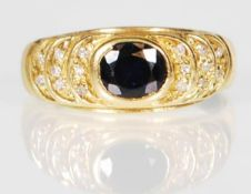 An 18ct gold ring set with an oval cut sapphire wi